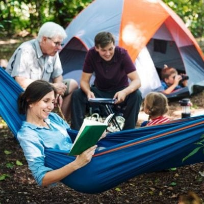 mom in a hammock reading a book with family around tent in campsite