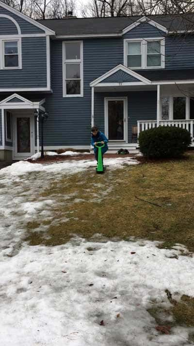 A boy on a snow scooter on the wet grass with a little snow in front of his home