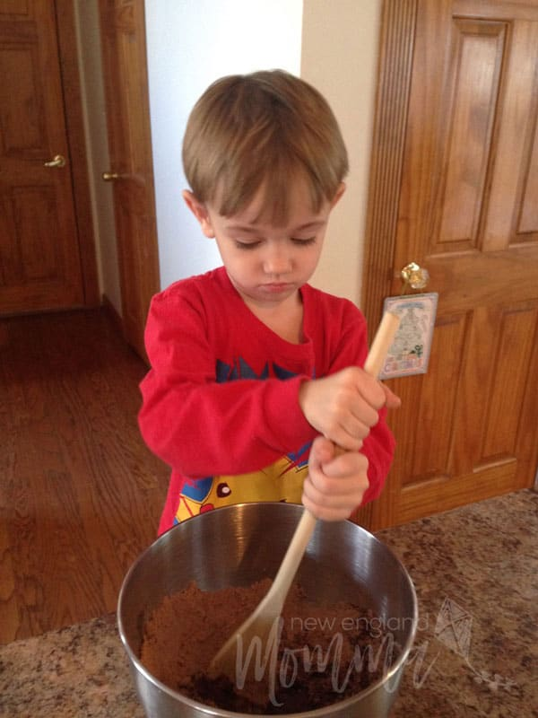 Young boy looking down as he mixes double chocolate cookie mix