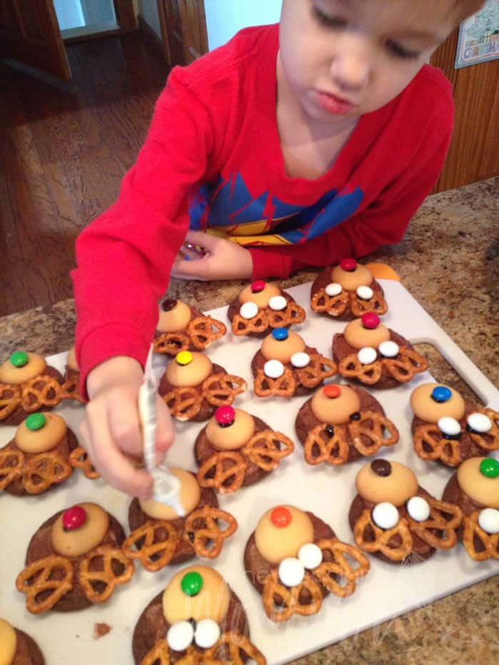 Toddler decorating cookies into reindeers with cookie wafers, pretzels and M&Ms.