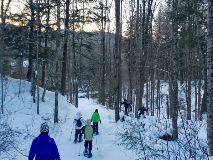 6 people of varying ages hiking through the woods on snowshoes on a wooded snowy trail