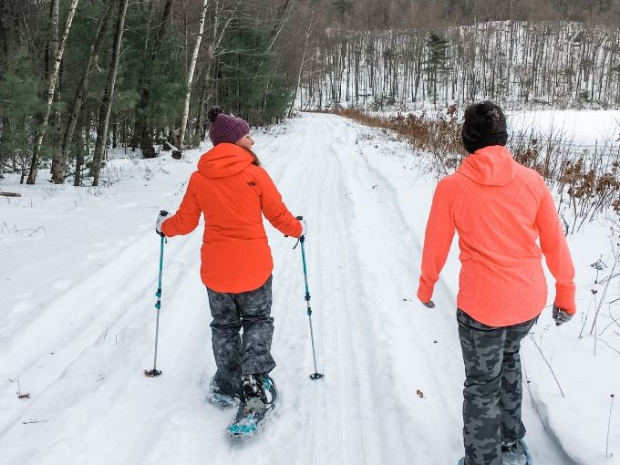 two women snowshoeing on a trail next to the woods