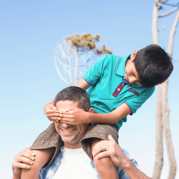 A dad with his young son on his shoulders happy outside.