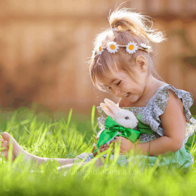 A little girl barefoot and sitting in the grass with a bunny