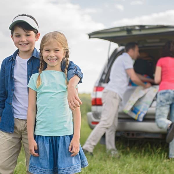 Mom, dad packing up the car while a boy and girl wait and smile