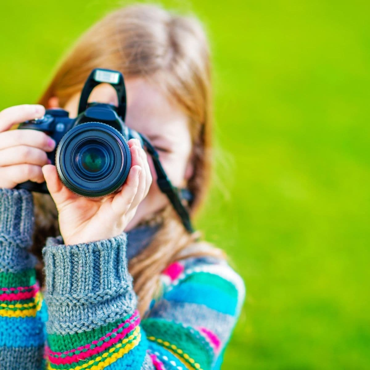 A girl outdoors with a camera taking pictures