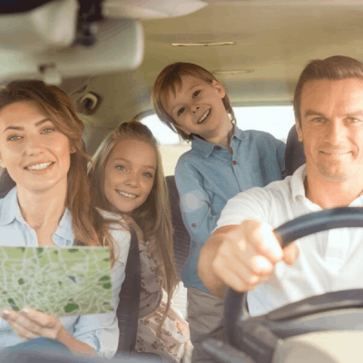 happy family of four with a map going on a road trip
