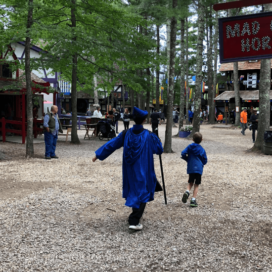 Two boys in costume at an outdoor Renaissance fair.