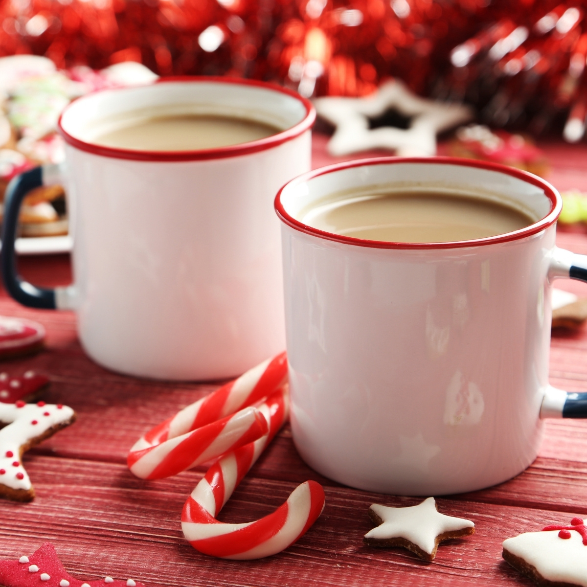 two mugs of hot cocoa in a festive red setting