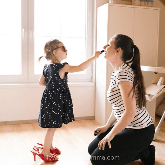 little girl putting makeup on her mom