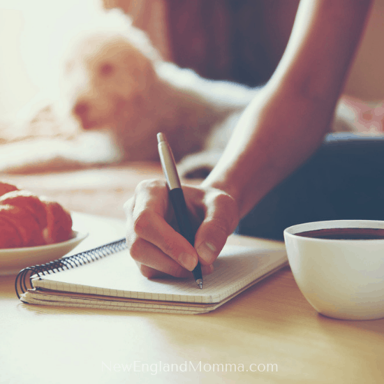 A woman relaxing while writing in journal with coffee and dog nearby