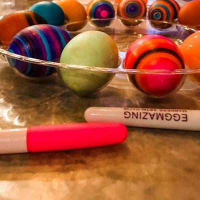 multiple Easter eggs decorated on the table with markers