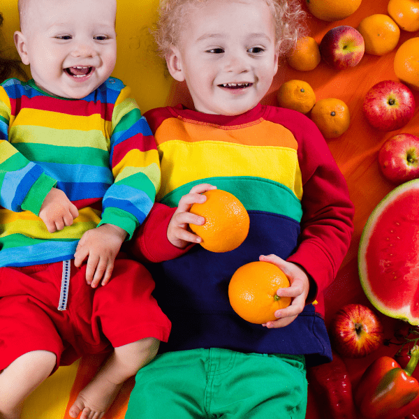 2 happy kids going on a car ride with a rainbow of fruits for car snacks