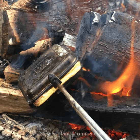 Pie iron in fire pit, cooking grilled cheese sandwich