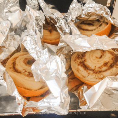 4 cinnamon rolls cooking up in oranges on the grill.