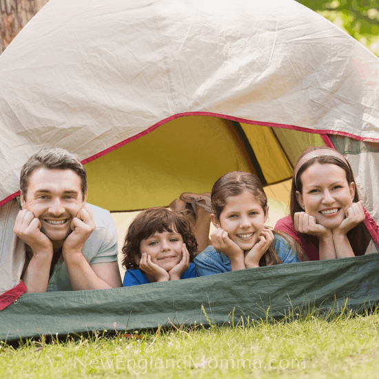 a family of four on their elbows smiling as the look out from a camping tent