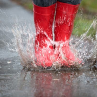 red boots splashing in puddles while camping in the rain