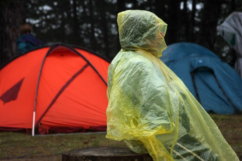 A camper in a rain poncho by a couple of tents waiting out the wet weather