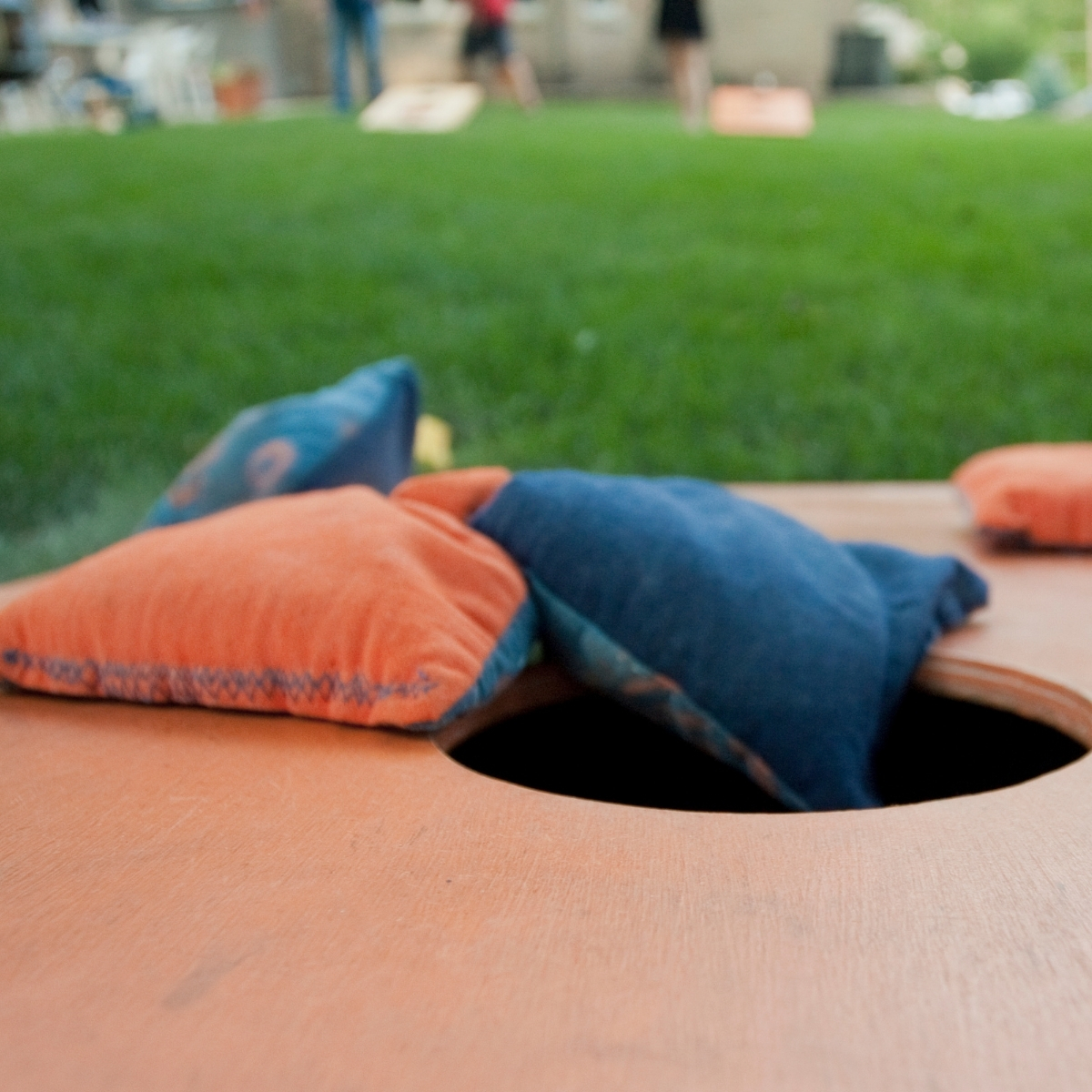 colorful bean bags on a corn hole board