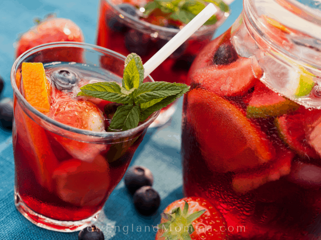 red sangria in a glass with a pitcher
