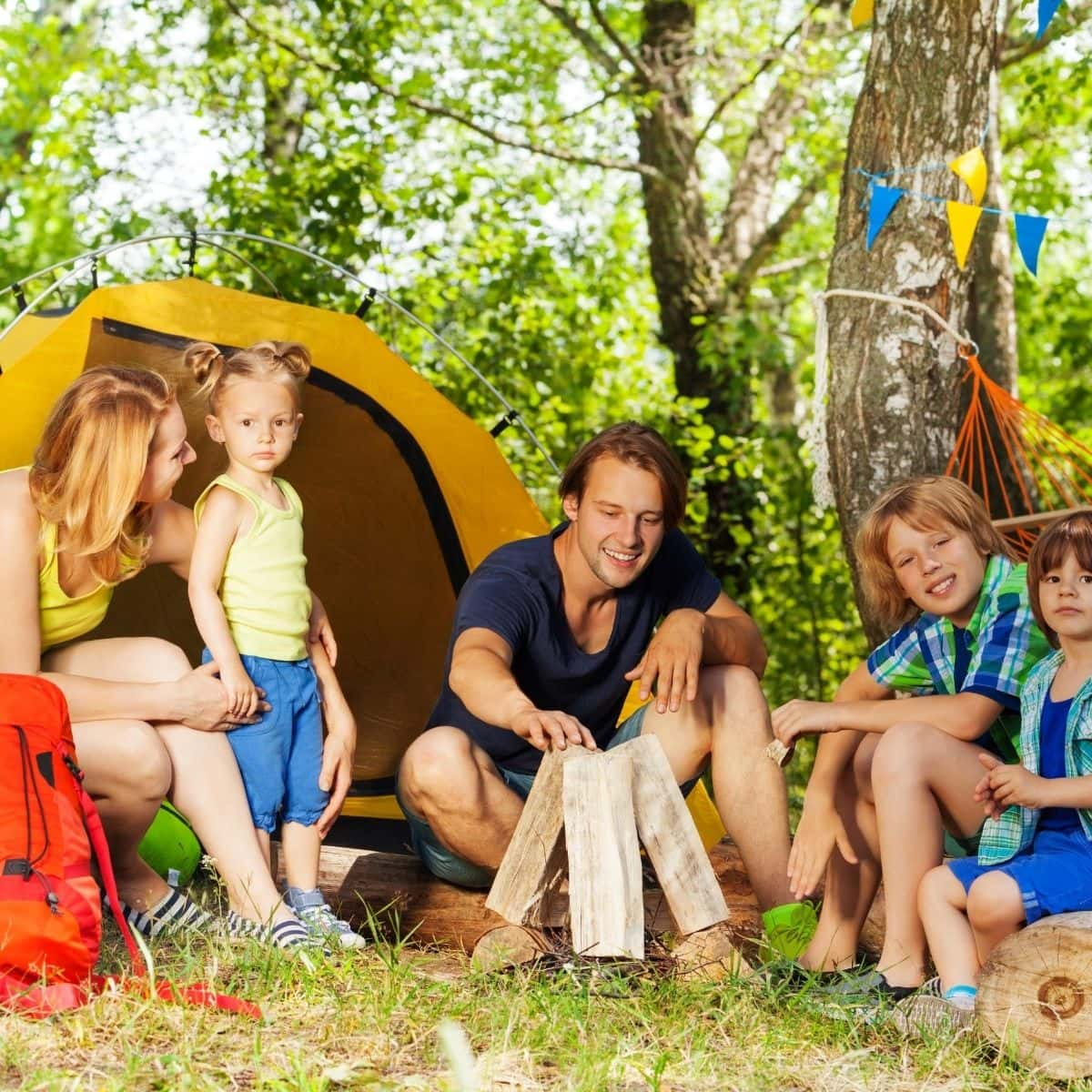 A family of 5 sitting on the ground next to a tent enjoying camping