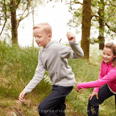 2 kids running in the woods and grass