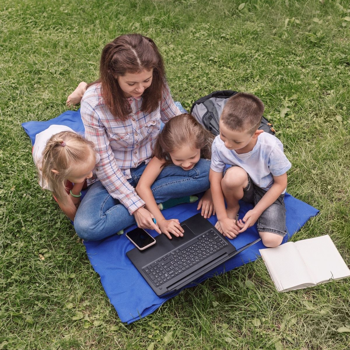mom and kids outdoors on a laptop planning a day trip