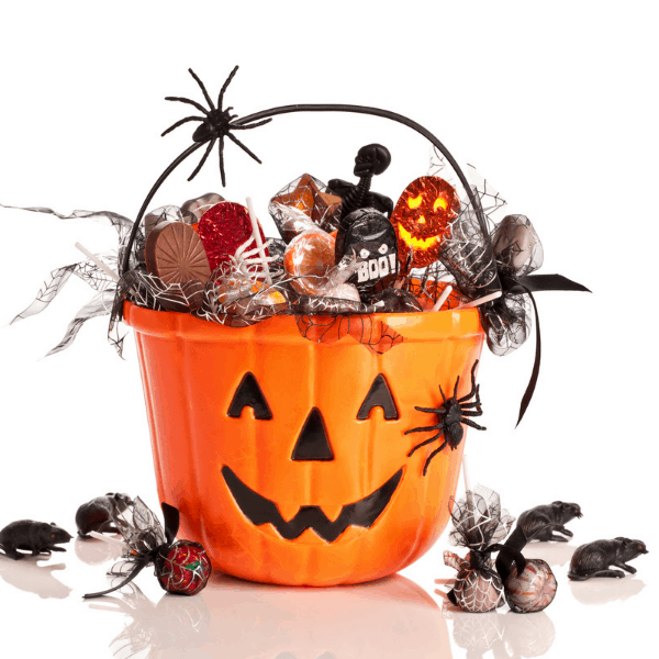 a pumpkin face basket filled with halloween candy and goodies