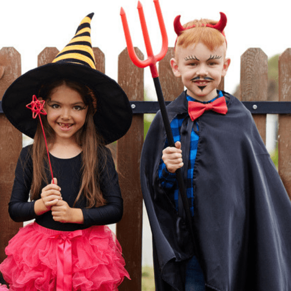 Kids dressed up in their Halloween costumes with big accessories like a witch hat or devil's pitch fork.