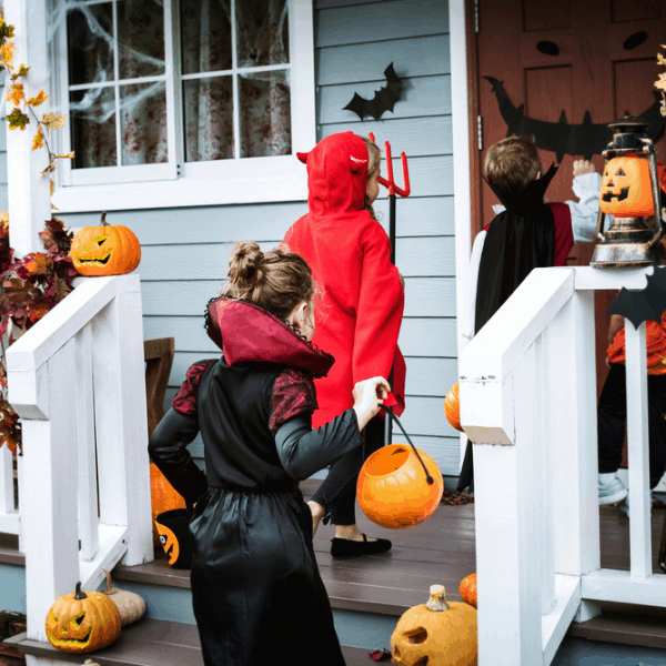 Kids in costumes trick or treating at a home with a decorated front porch