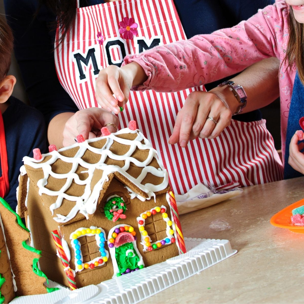 Kids and mom decorating a gingerbread house