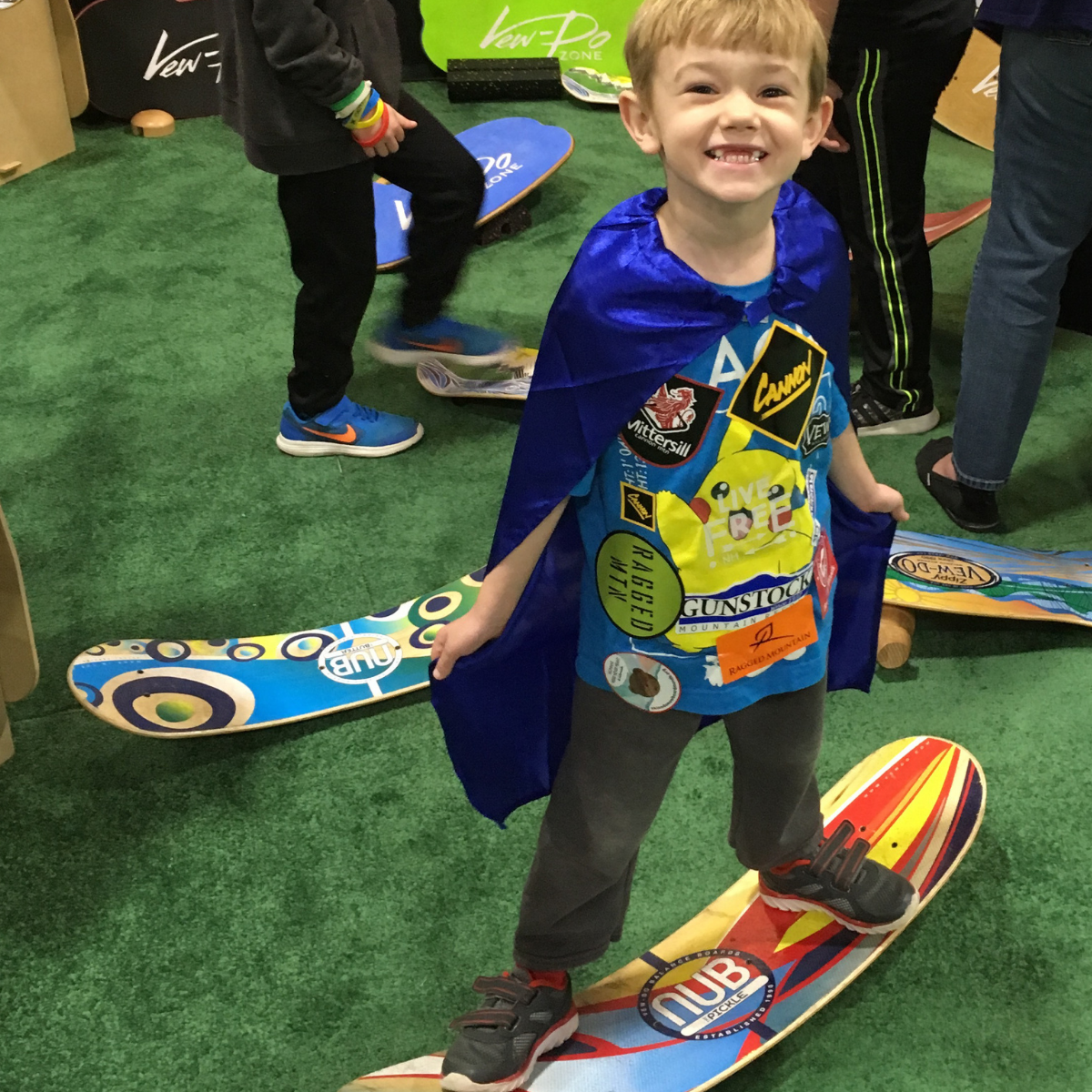 young boy at indoor expo on a snowboard