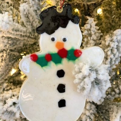 melted bead snowman ornament on a tree branch