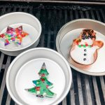 homemade Christmas bead ornaments in pans on a gas grill