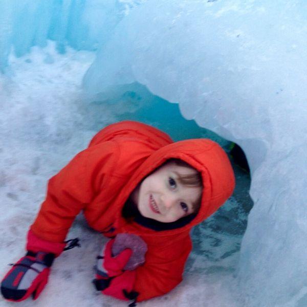 little boy crawling through an ice tunnel