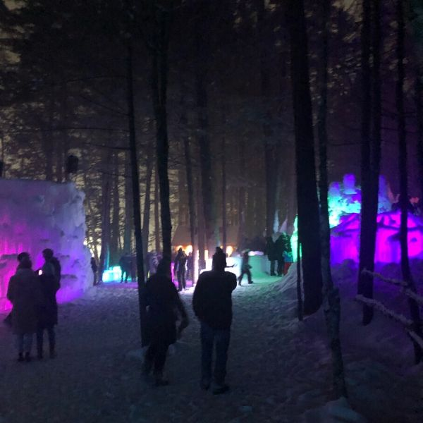 People walking around at night with colorful lit up ice walls at Ice Castles.