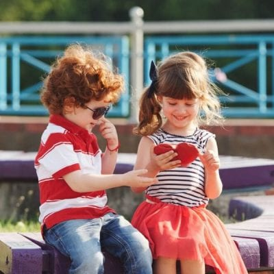 little boy and a little girl sitting together with a small red heart Valentine's Day card
