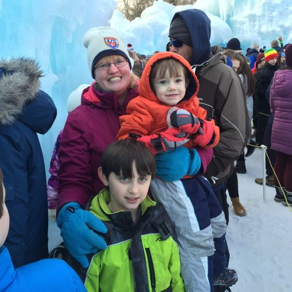 A mom and two boys dressed in warm winter clothes waiting in line at the Ice Castles