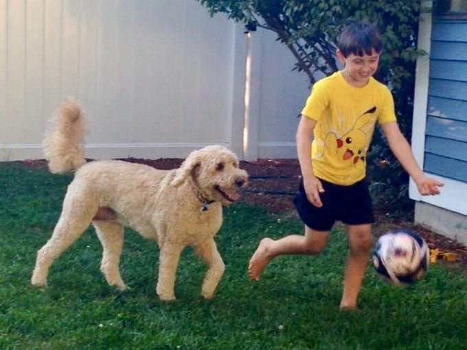 happy boy playing soccer with dog in backyard