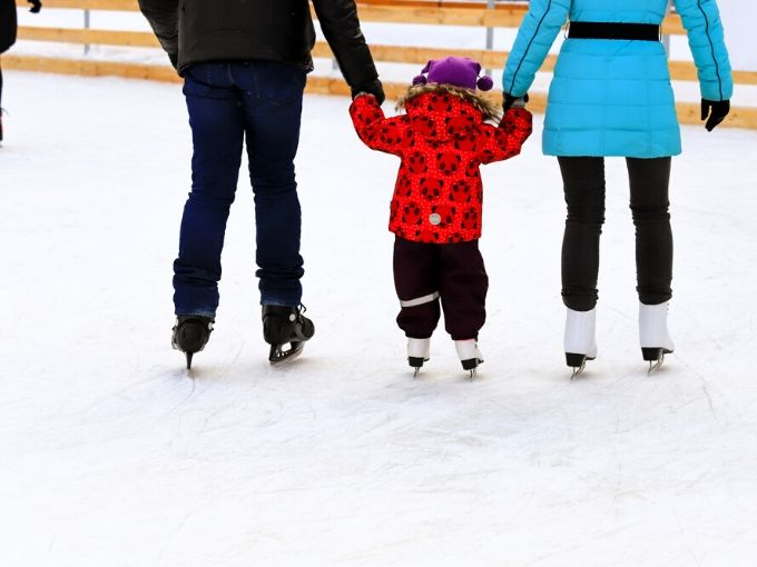 Mom, dad and child holding hands skating away from us