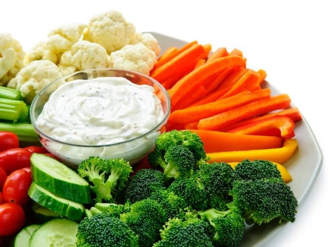 raw vegetables on a round tray with a white ranch dip in the center