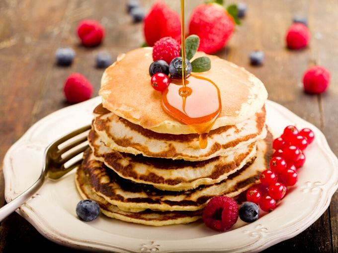 a stack of 5 pancakes with various berries and maple syrup with a fork