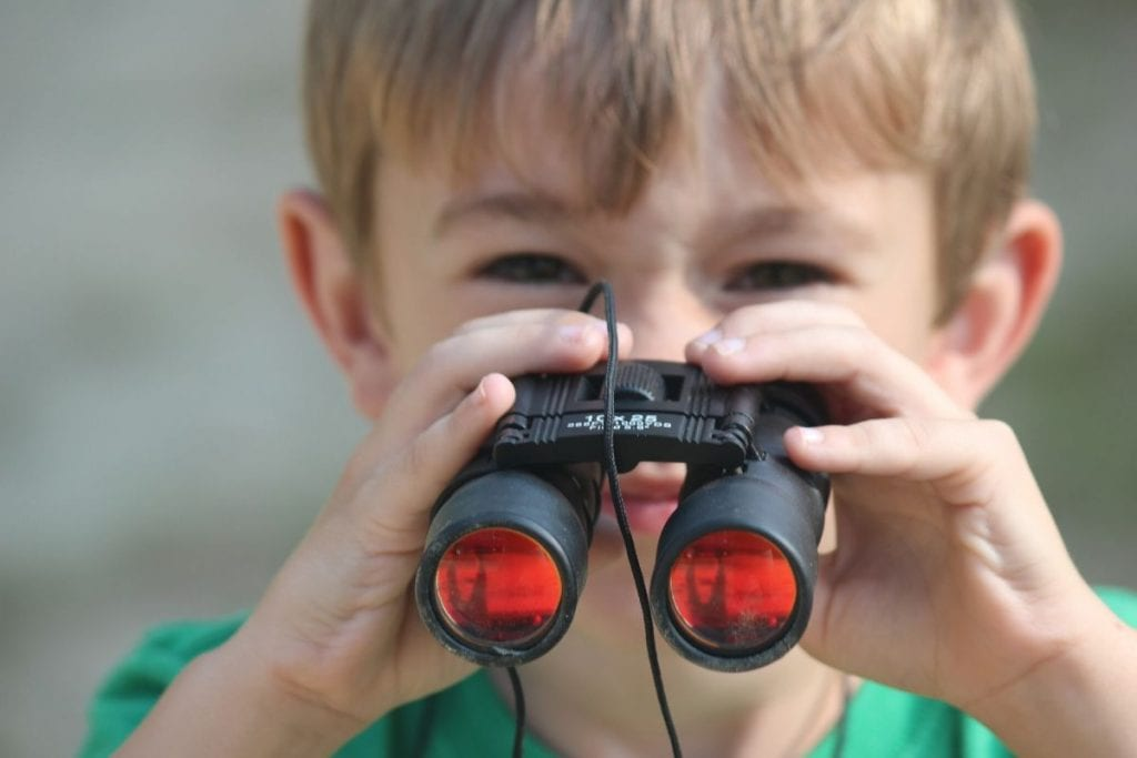 young boy looking through binoculars wearing a green shirt