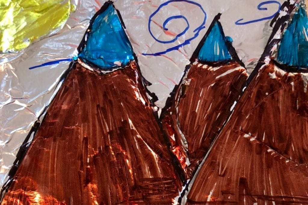 tin foil paper with picture of mountains with sun hand drawn with markers