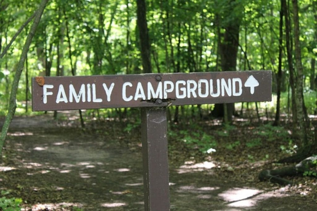 a brown wooden sign with white painted letters spellign out Family Campground with an arrow in the woods.