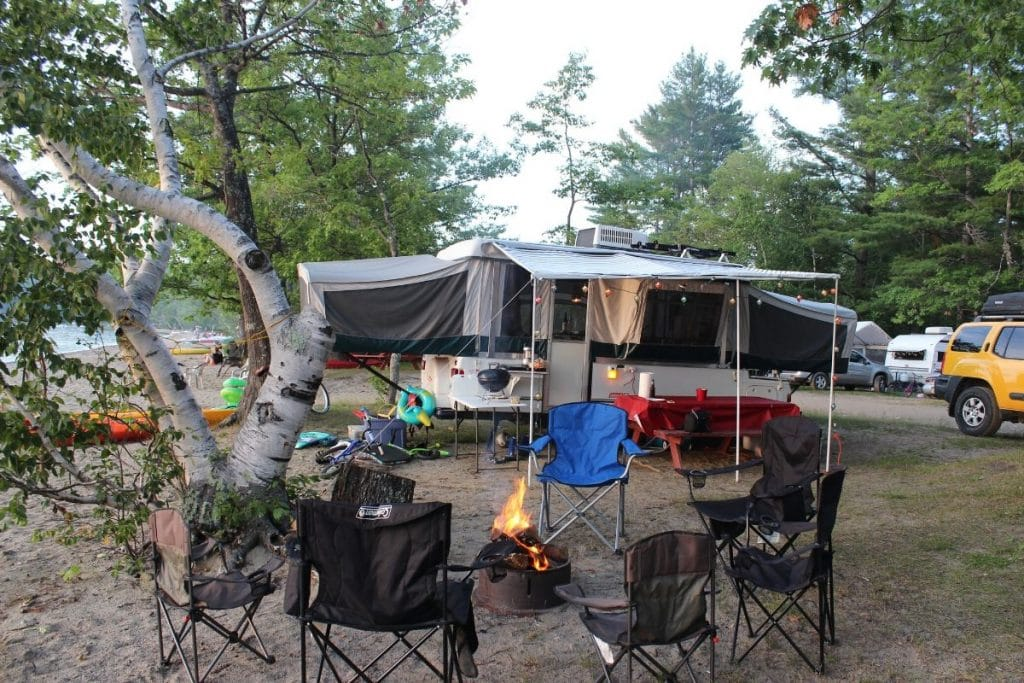 a pop up trailer with a campfire and camp chairs around it.