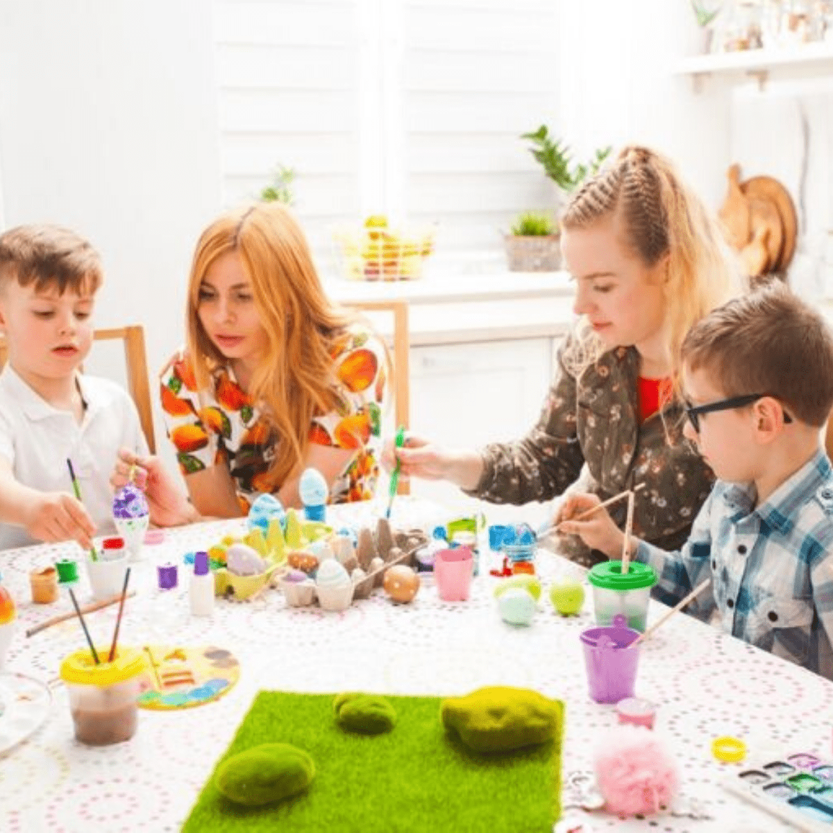 two moms and two boys decorating Easter eggs at a table with paint