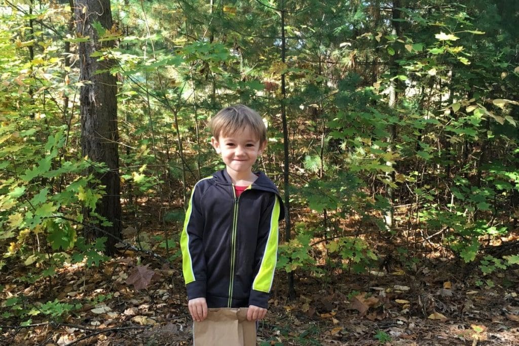 young boy on a hike with a brown paper bag in the woods to collect nature treasure