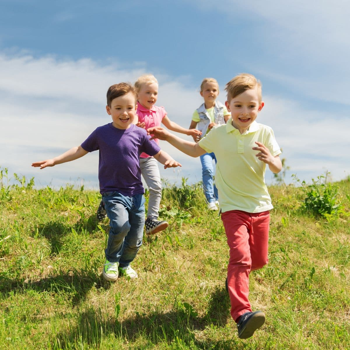 4 kids running in a field with big smiles