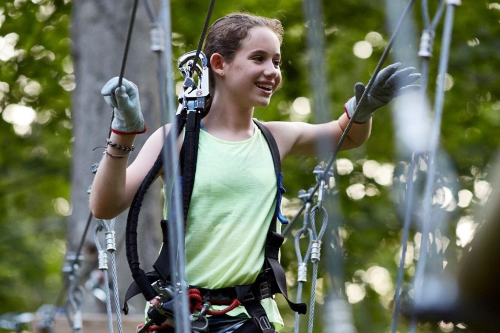 Young teen girl with gloves and harness on a rope course